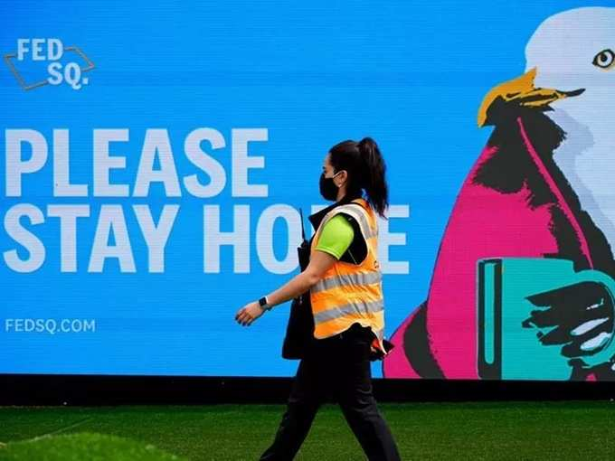 FILE PHOTO_ An essential worker walks past a Please Stay Home sign on the first day of a five-day COVID-19 lockdown in Melbourne.