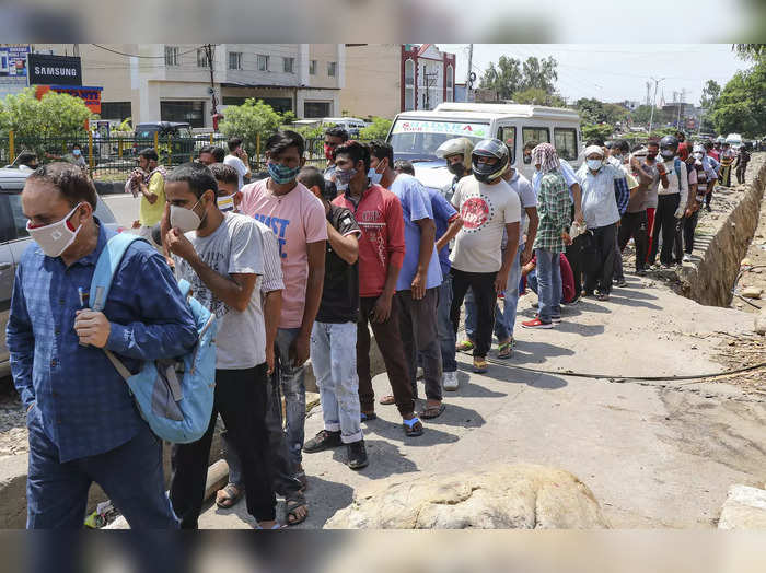 Jammu: People wait in a long queue to buy liquor from a wine shop after the ease...