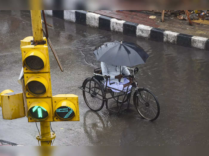 New Delhi: A man protects himself from rains in New Delhi, May 19, 2021. (PTI Ph...