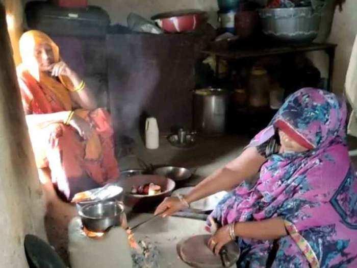 चूल्हे पर खाना बना रही हैं महिलाएं