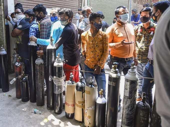 New Delhi_ Family members of COVID-19 patients wait outside an oxygen-filling ce....