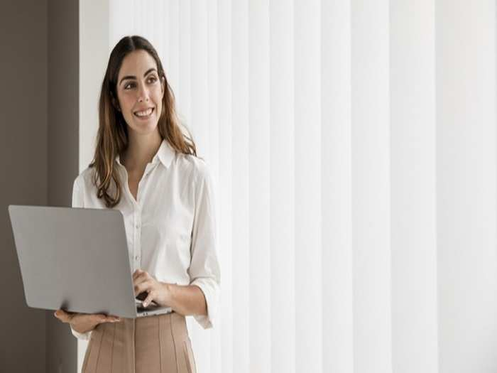 front-view-smiley-elegant-businesswoman-using-laptop-with-copy-space_23-2148788848