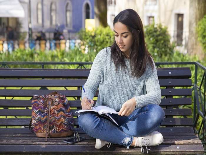 serious-woman-making-notes-sitting-bench-outdoors