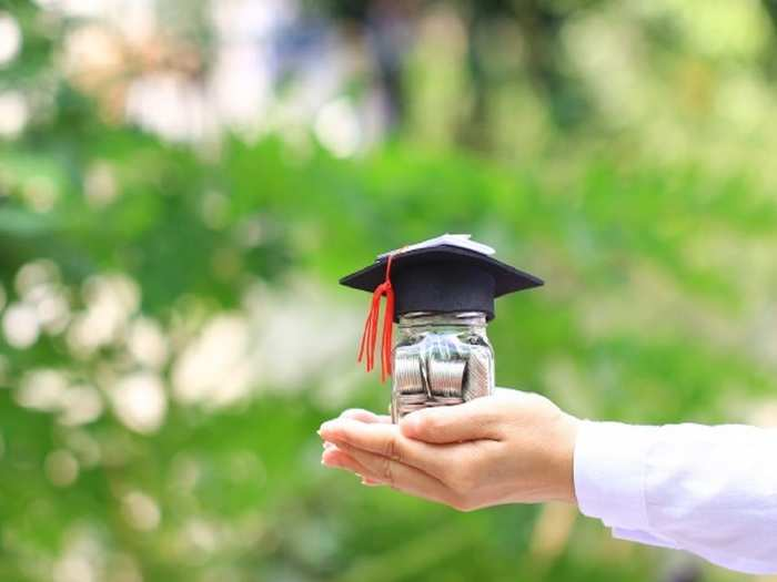 woman-hand-holding-coins-money-glass-bottle-with-graduates-hat-natural-green-background_106094-133