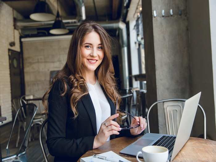 widely-smiling-businesswoman-working-laptop-sitting-cafe