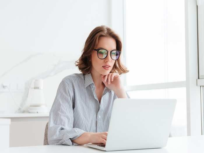 charming-businesswoman-glasses-striped-shirt-working-with-laptop-computer-while-siting-home
