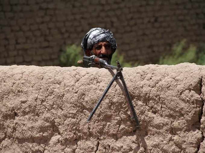 مجاهد سابق يقف حراسة عند نقطة تفتيش وهو يحمل سلاحًا لدعم القوات الأفغانية في قتالها ضد طالبان في ضواحي مقاطعة هرات.