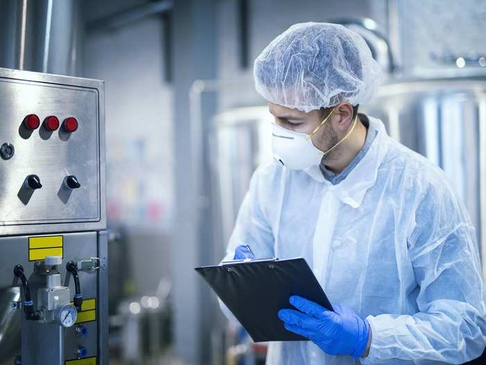 technologist-expert-protective-uniform-with-hairnet-mask-taking-parameters-from-industrial-machine-food-production-plant