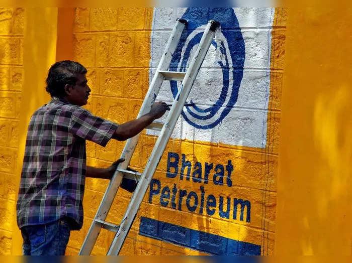 A man paints the logo of oil refiner Bharat Petroleum Corp