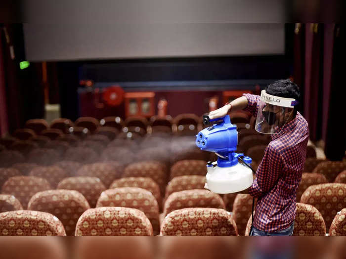 New Delhi: A worker fumigates inside Delite Cinema Hall, a day ahead of the open...
