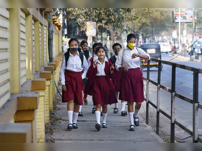 Guwahati: Students wearing face masks walk along a street to reach their school,...