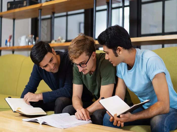 three-fellow-students-reading-textbook-preparing-exam