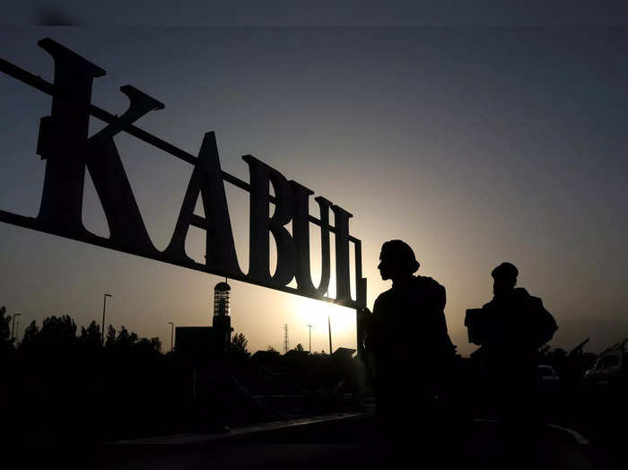 FILE PHOTO: Taliban soldiers stand in front of a sign at the international airport in Kabul