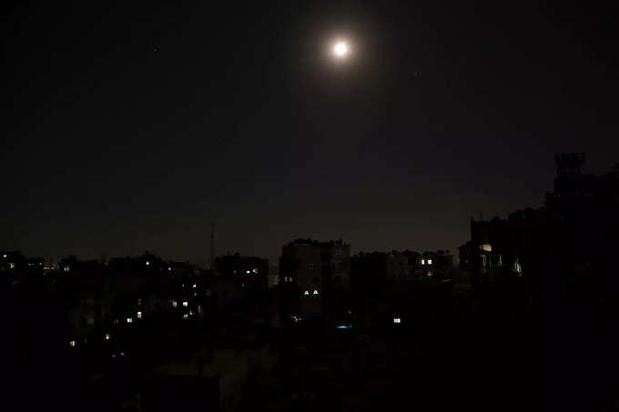 A view shows unlit residential buildings during a power cut in Damascus